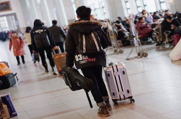 Mann mit Handgepäck und Gitarre