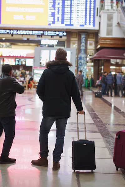 Mann mit Handgepäck an Flughafen