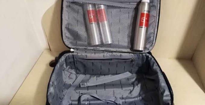 Drei Dosen Haarspray und ein schwarzer Handgepäckkoffer