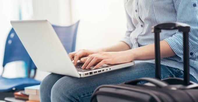 Bild zeigt eine Passagierin am Flughafen mit Handgepäck und Laptop