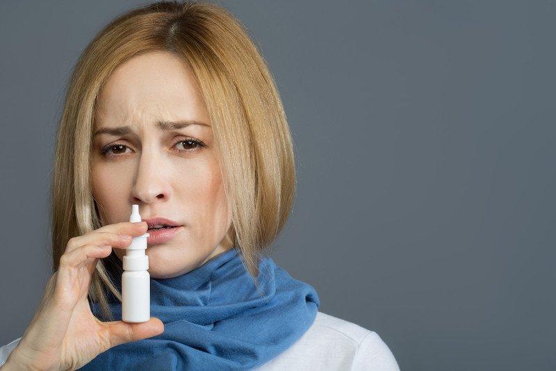 Bild zeigt eine Frau, die sich Nasenspray in die Nase spritzt.