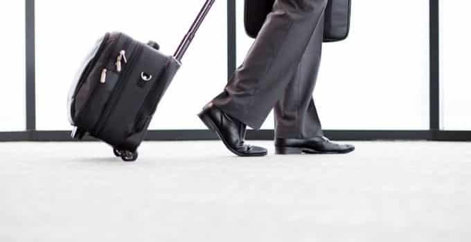Bild zeigt einen Mann mit Koffer am Flughafen. Fokus auf Beine und Koffer