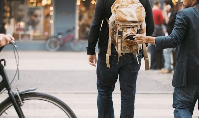 Bild zeigt einen Dieb, der einem Reisenden einen Brieftasche entwendet